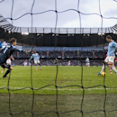 With Stoke goalkeeper Asmir Begovic, left, stranded, Manchester City's Edin Dzeko, right, misses an open goal during their English Premier League soccer match at the Etihad Stadium, Manchester, England, Saturday, Feb. 22, 2014