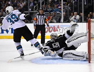 Los Angeles Kings goalie Jonathan Quick, right, tangles with San Jose Sharks center Logan Couture during the third period in Game 3 of an NHL hockey first-round playoff series, Tuesday, April 22, 2014, in Los Angeles. (AP Photo/Mark J. Terrill)