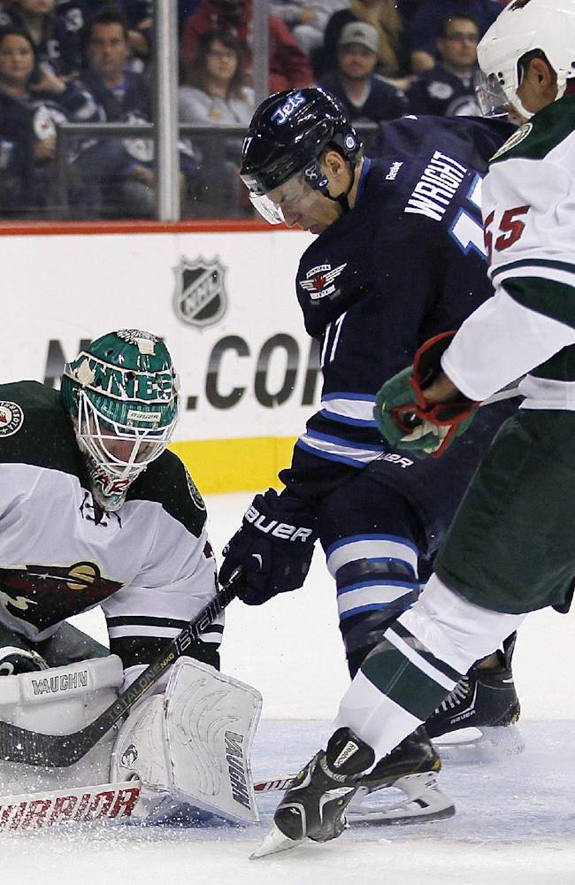 Minnesota Wild goaltender Josh Harding (37) gets his pad on a shot from Winnipeg Jets' James Wright (17) as Wild's Mathew Dumba (55) watches for the rebound during second-period preseason NHL hockey game action in Winnipeg, Manitoba, Thursday, Sept. 19, 2013