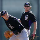 Colorado Rockies shortstop Troy Tulowitzki gets ready to throw to first base as teammate Charlie Culberson looks on during a spring training baseball practice Wednesday, Feb. 26, 2014, in Scottsdale, Ariz The Associated Press
