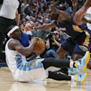 Denver Nuggets guard Ty Lawson, left, looks to pass the ball as he falls to the floor while New Orleans Pelicans guard Jrue Holiday covers in the first quarter of an NBA basketball game in Denver on Sunday, Dec. 15, 2013 The Associated Press