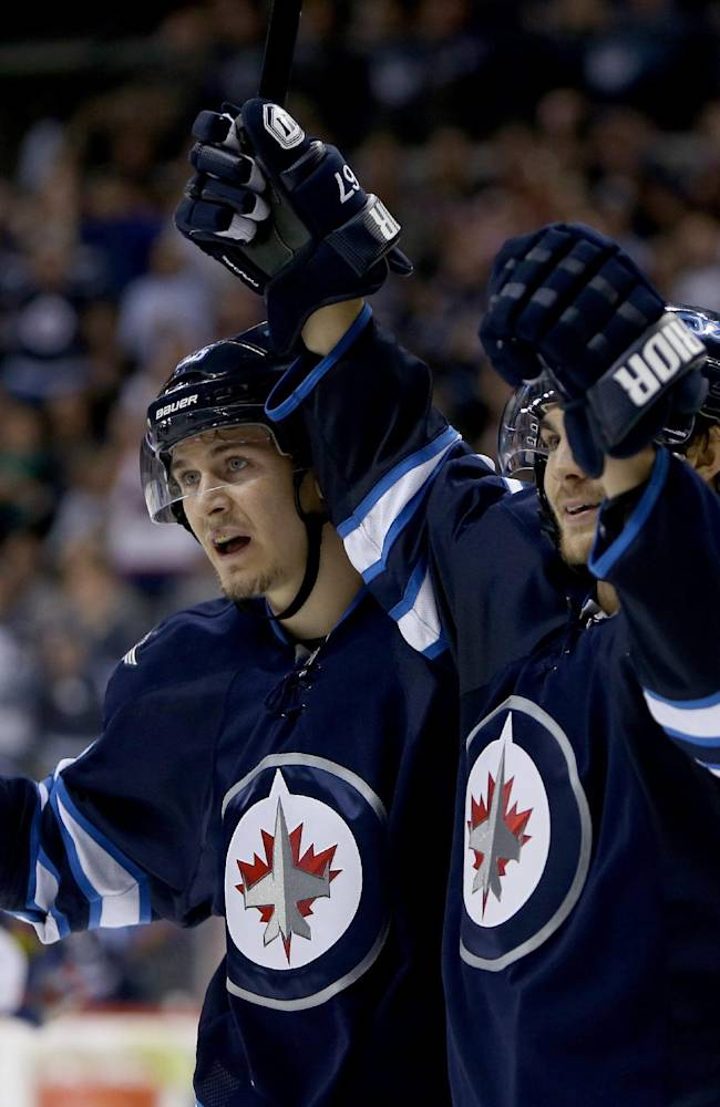 Winnipeg Jets' Mark Scheifele (55) and Michael Frolik (67) celebrate after Frolik scored against the Edmonton Oilers during the second period of a preseason NHL hockey game in Winnipeg, Manitoba, Tuesday, Sept. 17, 2013