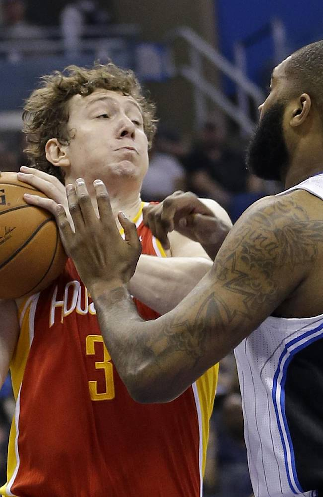 Houston Rockets' Omer Asik (3) tries to keep the ball from Orlando Magic's Kyle O'Quinn (2) on a rebound during the first half of an NBA basketball game in Orlando, Fla., Wednesday, March 5, 2014