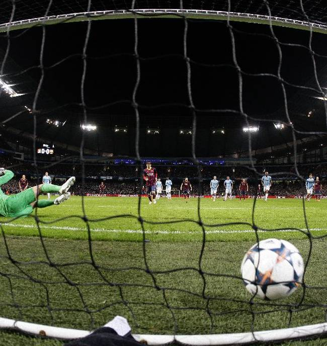 Barcelona's Lionel Messi scores the first goal of the game from a penalty during the Champions League first knock out round soccer match between Barcelona and Manchester City at the Etihad Stadium, Manchester, England, Tuesday Feb. 18, 2014