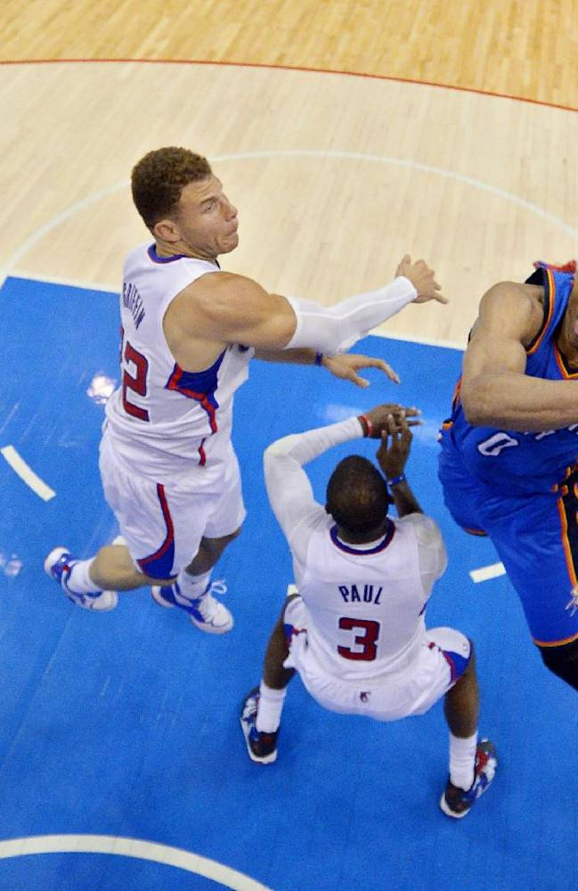 Oklahoma City Thunder guard Russell Westbrook, right, shoots as Los Angeles Clippers forward Blake Griffin, left, and guard Chris Paul (3) defend and guard Jamal Crawford looks on in the second half of Game 3 of the Western Conference semifinal NBA basketball playoff series, Friday, May 9, 2014, in Los Angeles. The Thunder won 118-112