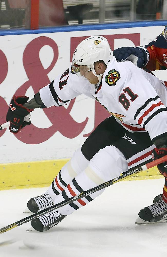 Chicago Blackhawks' Marian Hossa (81) and Florida Panthers' Matt Gilroy (97) chase the puck during the second period of an NHL hockey game in Sunrise, Fla., Tuesday, Oct. 22, 2013