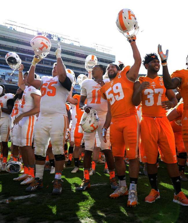 Tennessee football players, including quarter Joshua Dobbs, center, rally on the field at the end of the Orange and White game at Neyland Stadium in Knoxville, Tenn., Saturday, April 12, 2014