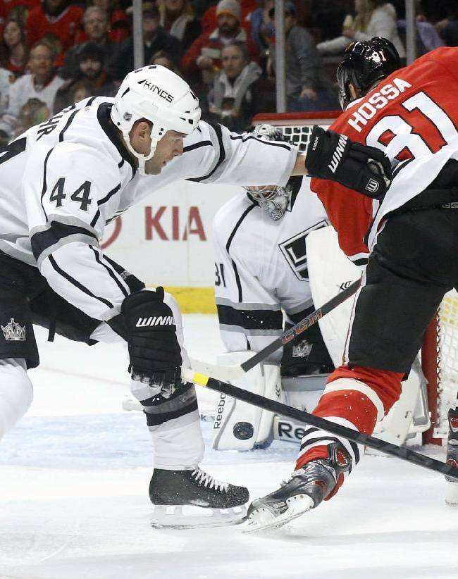 Los Angeles Kings goalie Martin Jones makes a save on a shot by Chicago Blackhawks right wing Marian Hossa (81) as defenseman Robyn Regehr (44) also defends during the second period of an NHL hockey game Monday, Dec. 30, 2013, in Chicago