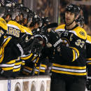 Boston Bruins defenseman Zdeno Chara is congratulated by teammates at the bench after scoring against the Phoenix Coyotes during the first period of an NHL hockey game in Boston Thursday, March 13, 2014. (AP Photo/Winslow Townson)