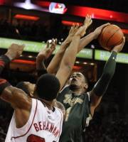 South Florida's Ron Anderson Jr., right, puts a shot up ovet the defense of Louisville's Chane Behanan, front, and Zach Price during the first half of their NCAA college basketball game on Wednesday, Feb. 29, 2012, in Louisville, Ky. (AP Photo/Timothy D. Easley)