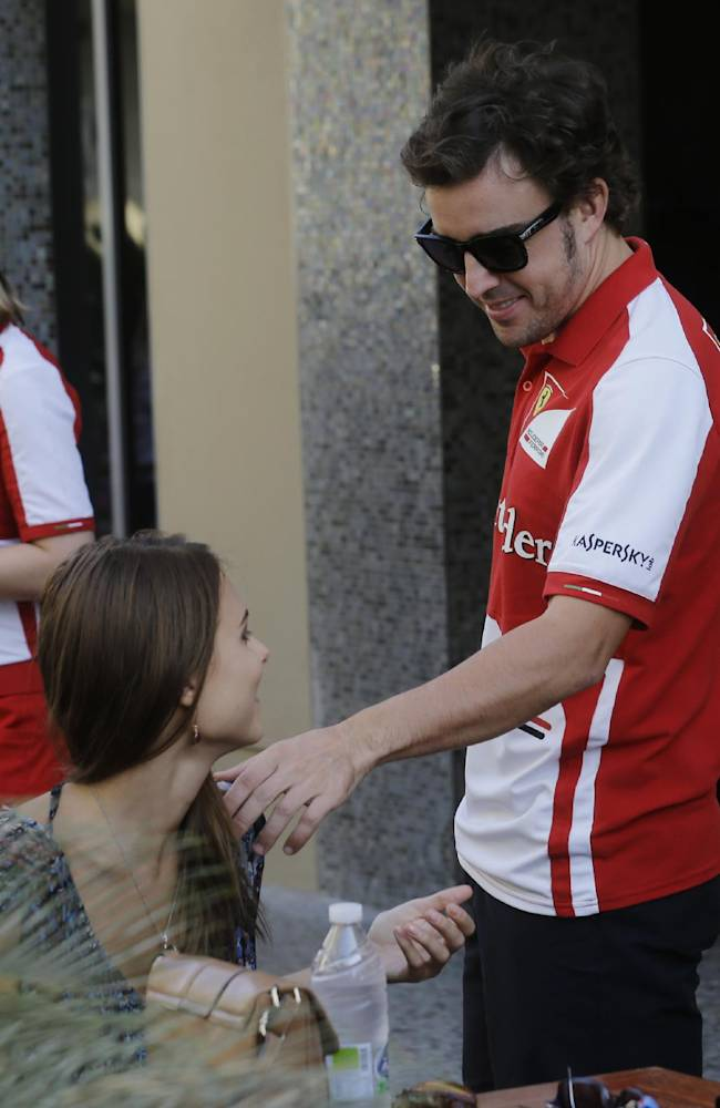 Ferrari driver Fernando Alonso of Spain, right, shares a moment with his girlfriend, Russian model Dasha Kapustina , prior to the start of the qualifying session at the Yas Marina racetrack in Abu Dhabi, United Arab Emirates, Saturday, Nov. 2, 2013