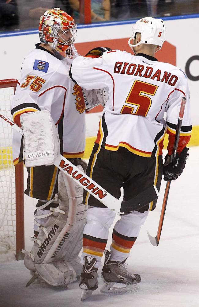 Calgary Flames goalie Joey MacDonald (35) and defenseman Mark Giordano (5) celebrate their win against the Florida Panthers after an NHL hockey game in Sunrise, Fla., on Friday, April 4, 2014. Calgary won 2-1