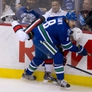 Vancouver Canucks defenseman Chris Tanev (8) goes into the boards with Ottawa Senators right wing Curtis Lazar during the first period of an NHL hockey game Tuesday, Nov. 11, 2014, in Vancouver, British Columbia The Associated Press