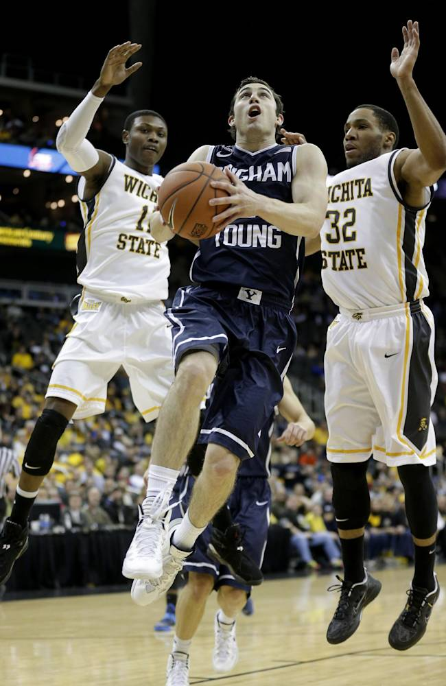 BYU's Matt Carlino, center, gets past Wichita State's Cleanthony Early, left, and Tekele Cotton (32) to put up a shot during the second half of an NCAA college basketball game Tuesday, Nov. 26, 2013, in Kansas City, Mo. Wichita State won 75-62