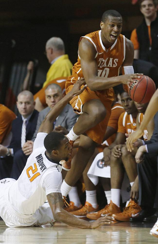Texas forward Jonathan Holmes (10) jumps over Oklahoma State post Kamari Murphy (21) in the second half of an NCAA college basketball game in Stillwater, Okla., Wednesday, Jan. 8, 2014. Oklahoma State won 87-74