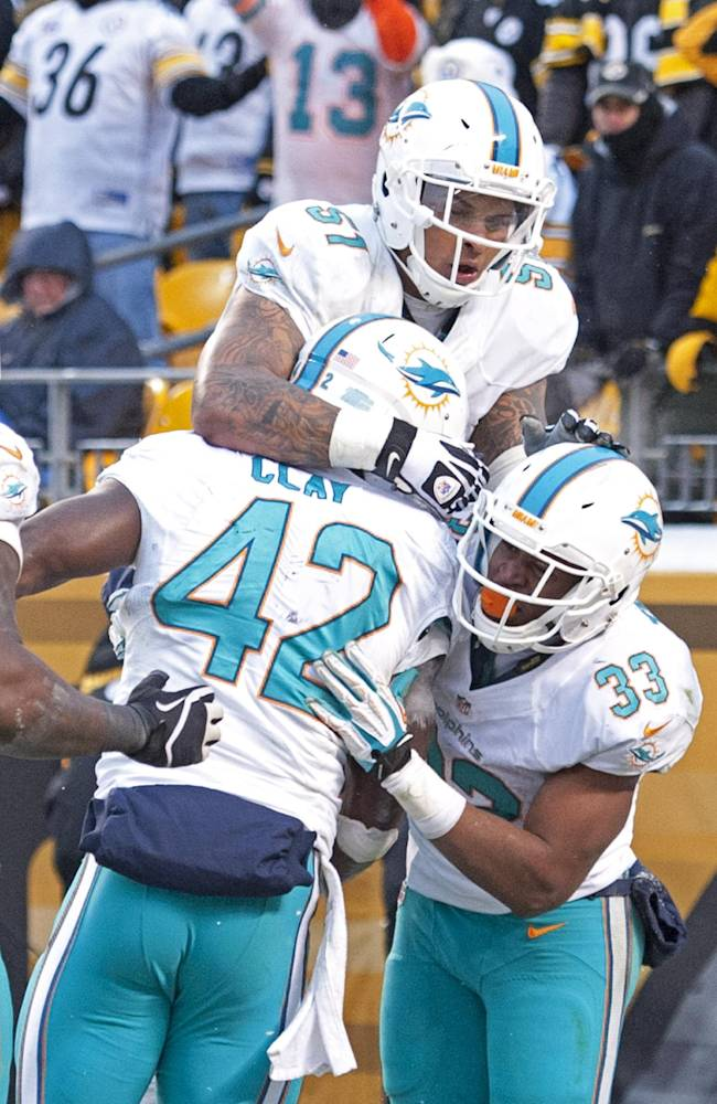 Miami Dolphins tight end Charles Clay (42) celebrates with Mike Pouncey (51) and Daniel Thomas (33) after scoring a touchdown during the second half of an NFL football game against the Pittsburgh Steelers in Pittsburgh, Sunday, Dec. 8, 2013