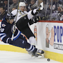 Winnipeg Jets' Jim Slater (19) checks Pittsburgh Penguins' Paul Martin (7) during the second period of an NHL hockey game in Winnipeg, Manitoba, on Thursday, April 3, 2014 The Associated Press