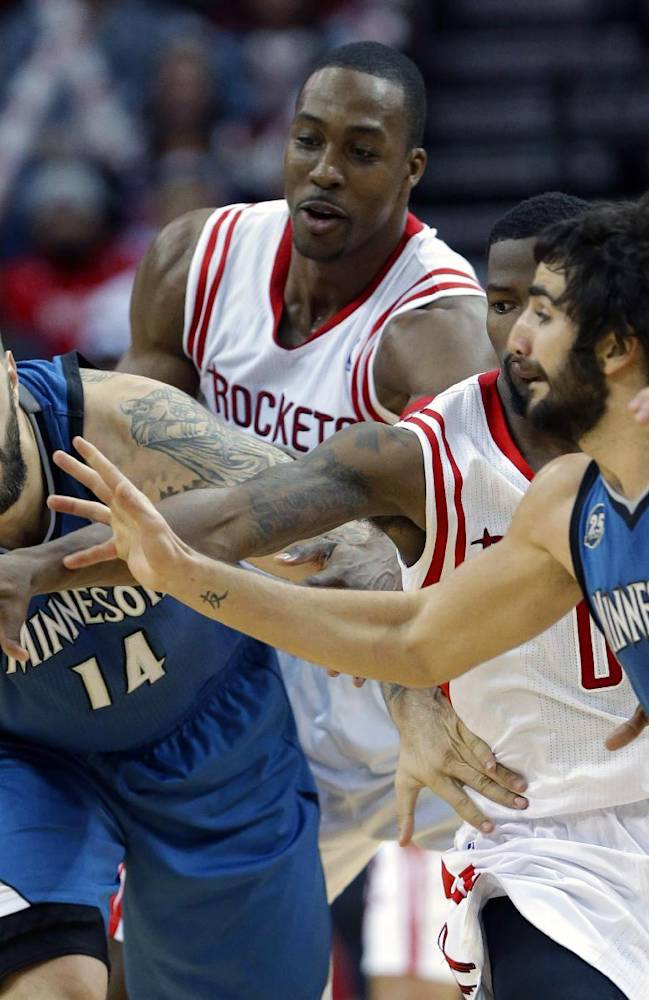 Minnesota Timberwolves' Nikola Pekovic (14) passes the ball off to Ricky Rubio (9) as Houston Rockets Dwight Howard, center, and Aaron Brooks (0) reach in in the second half of an NBA basketball game Saturday, Nov. 23, 2013, in Houston. The Rockets won 112-101