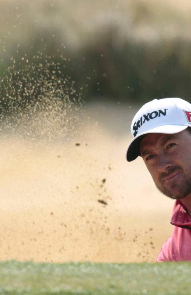 Graeme McDowell of Northern Ireland hits out of a bunker on the 2nd hole during the first round of the BMW Masters golf tournament at the Lake Malaren Golf Club in Shanghai, China, Thursday, Oct. 24, 2013. (AP Photo)