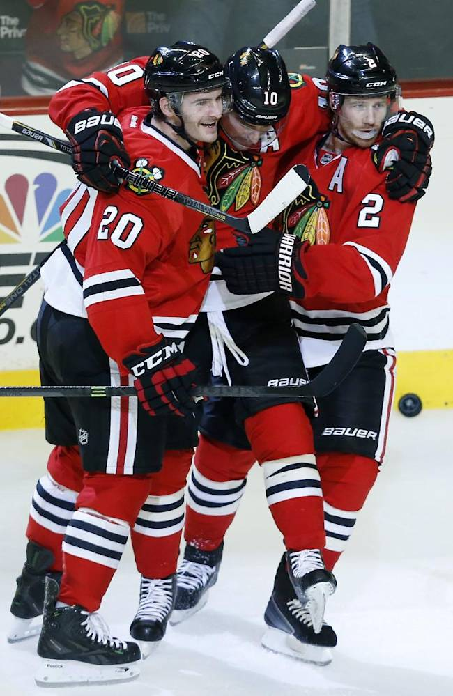 Chicago Blackhawks left wing Brandon Saad (20), left wing Patrick Sharp, center, and defenseman Duncan Keith (2) celebrate after Sharp scored a goal against the San Jose Sharks during the second period of an NHL hockey game on Sunday, Nov. 17, 2013, in Chicago