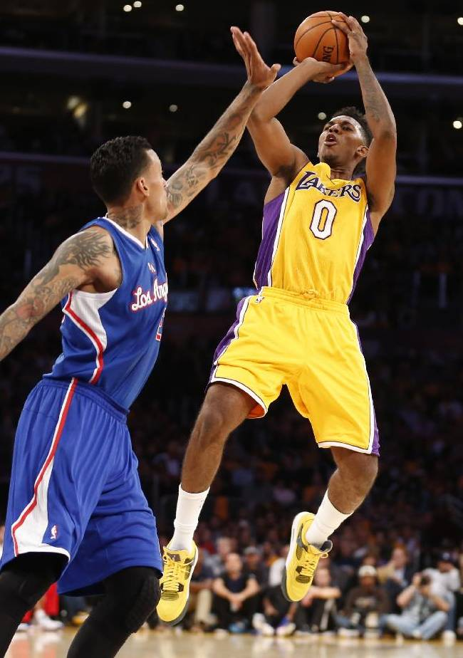 Los Angeles Lakers' Nick Young, right, shoots over Los Angeles Clippers' Matt Barnes, left, during the first half of an NBA basketball game in Los Angeles, Tuesday, Oct. 29, 2013