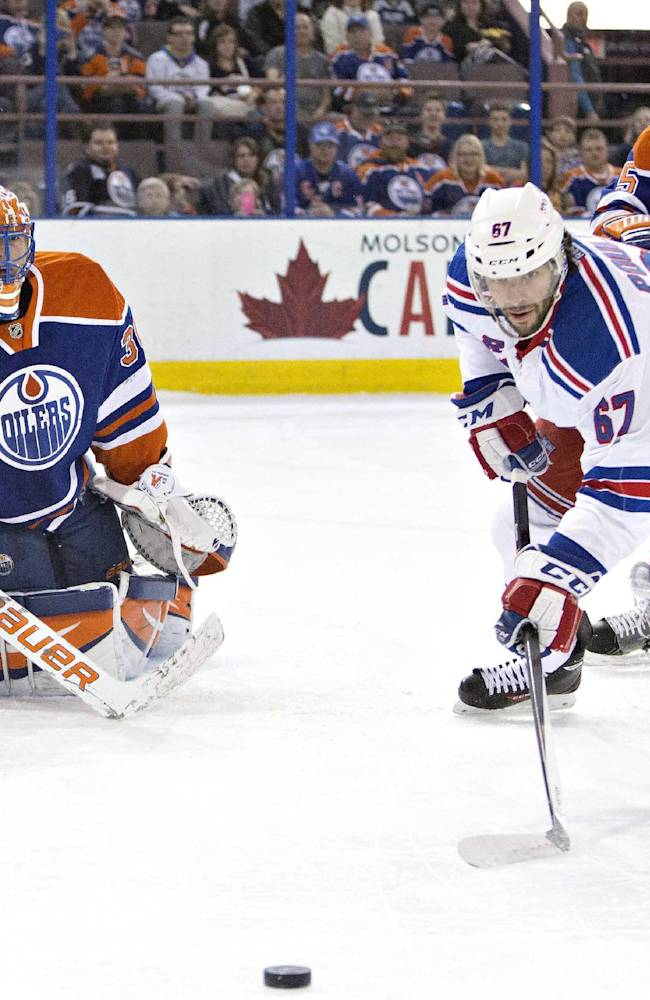 New York Rangers Benoit Pouliot (67) is crossed checked by Edmonton Oilers Mark Fraser (5) as Ben Scrivens (30) makes the save during first period NHL hockey action in Edmonton, Alberta., on Sunday March 30, 2014