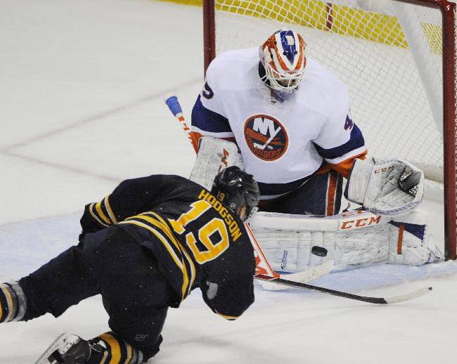 Buffalo Sabres' Cody Hodgson (19) falls as he shoots the puck on New York Islanders' Anders Nilsson, right, of Sweden, during the third period of an NHL hockey game in Buffalo, N.Y., Sunday, April 13, 2014. New York won 4-3 in a shootout