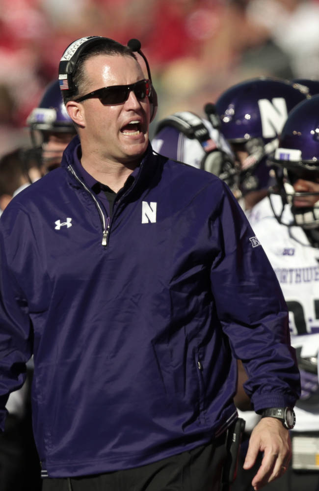Northwestern coach Pat Fitzgerald directs his team during the first half of an NCAA college football game in Madison, Wis., Saturday, Oct. 12, 2013. Wisconsin upset Northwestern 35-6