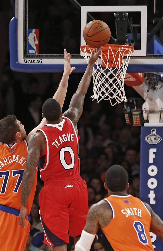 Atlanta Hawks' Jeff Teague (0) shoots against New York Knicks' Andrea Bargnani (77), of Italy, as J.R. Smith (8) and Carmelo Anthony (7) look on during the first half of an NBA basketball game Saturday, Nov. 16, 2013, in New York