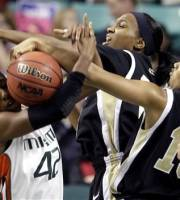Miami's Shenise Johnson, left, is blocked by Wake Forest's Mykala Walker, right, and Secily Ray, center, during the first half of an Atlantic Coast Conference NCAA college basketball tournament game in Greensboro, N.C., Friday, March 2, 2012. (AP Photo/Chuck Burton)