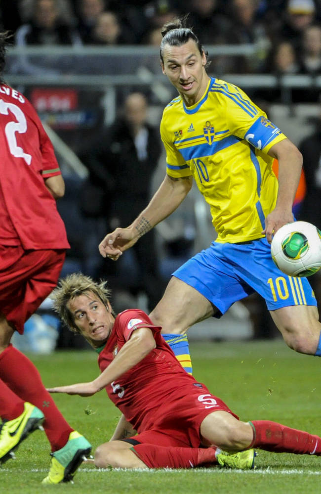 Sweden's Zlatan Ibrahimovic, right, fights for the ball with Portugal's Bruno Alves, left, and Fabio Coentrao during the World Cup 2014 qualifying playoff second leg soccer match between Sweden and Portugal at Friends Arena in Stockholm, Tuesday, Nov. 19, 2013.  (AP/Erik Martensson, TT)    SWEDEN OUT