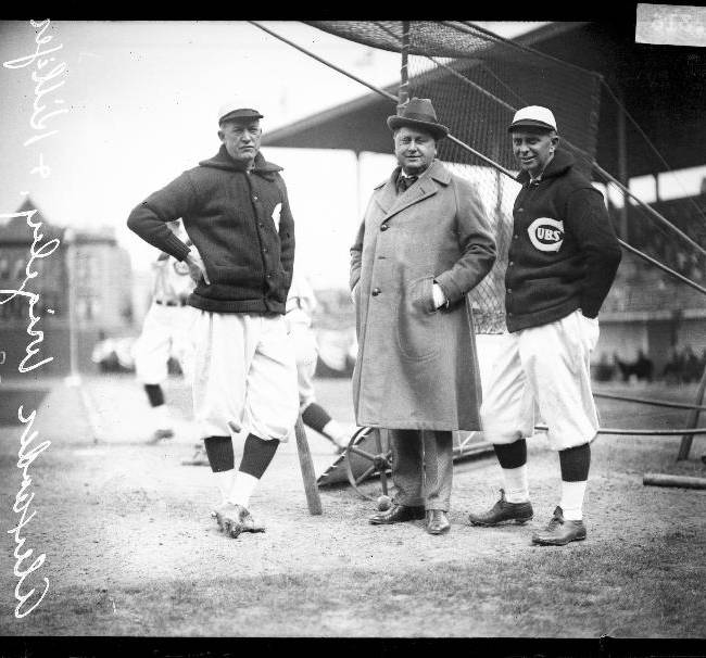 This 1922 photo provided by the Chicago History Museum shows from left, Chicago Cubs baseball player Pete Alexander, team owner William Wrigley Jr., and manager Bill Killefer standing behind a batting practice backstop on the field at Weeghman Park, in Chicago. Weeghman Park was renamed Wrigley Field in 1927. The famed ballpark will celebrate it's 100th anniversary on April 23, 2014