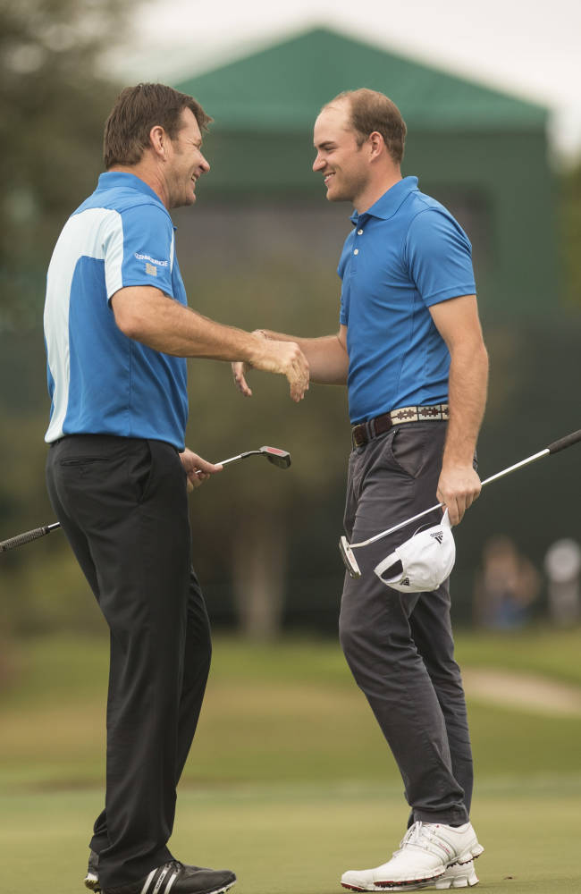 Nick Faldo and smiles with his son Matthew Faldo after the 18th hole during the Father-Son Challenge at the Ritz-Carlton Golf Club in Orlando, Fla., Sunday, Dec. 15, 2013