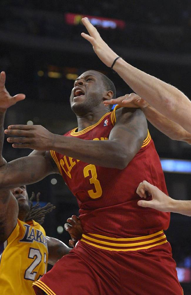 Cleveland Cavaliers guard Dion Waiters, second from left, puts up a shot as Los Angeles Lakers center Jordan Hill, left, guard Wesley Johnson, second fro right, and center Chris Kaman defend during the second half of an NBA basketball game, Tuesday, Jan. 14, 2014, in Los Angeles