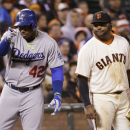 Los Angeles Dodgers' Yasiel Puig, left, points to his dugout after a triple next to San Francisco Giants third baseman Pablo Sandoval during the eighth inning of a baseball game on Tuesday, April 15, 2014, in San Francisco The Associated Press