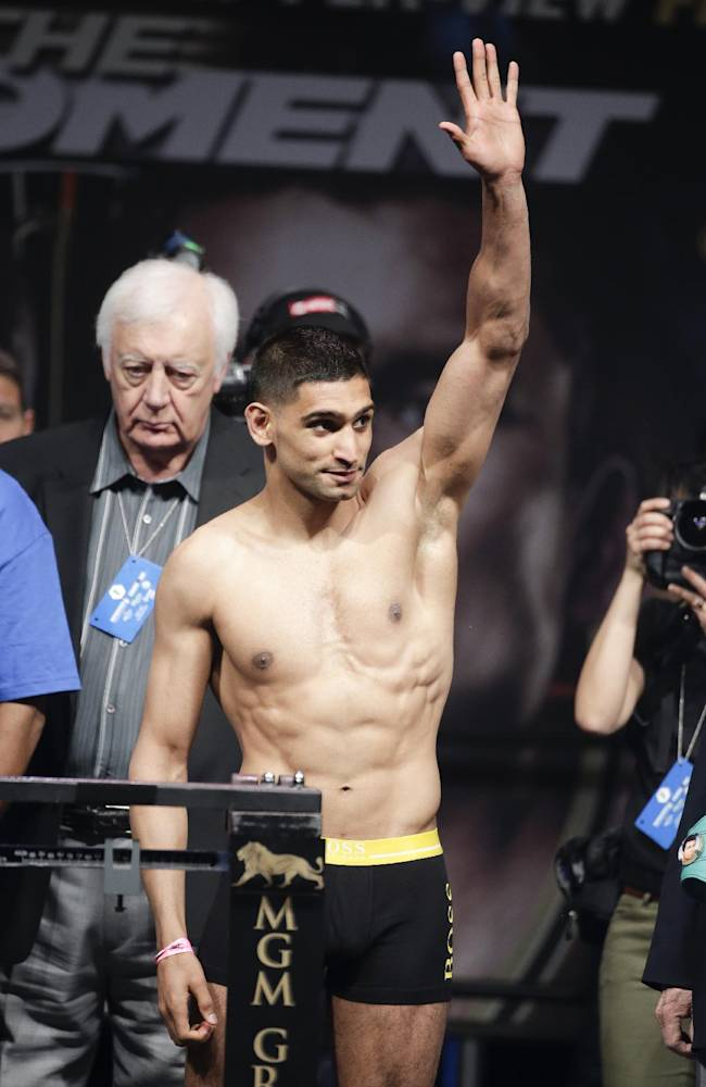 Amir Khan poses on the scales during the official weigh-in at the MGM Grand Hotel in Las Vegas, Friday, May 2, 2014. Khan is to face Luis Collazo in a 12-round bout for the vacant WBC silver welterweight world title on Saturday