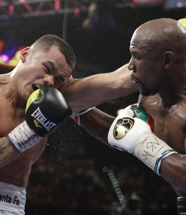 Marcos Maidana, left, from Argentina, trades blows with Floyd Mayweather Jr. in their WBC-WBA welterweight title boxing fight Saturday, May 3, 2014, in Las Vegas. Mayweather won the bout by majority decision