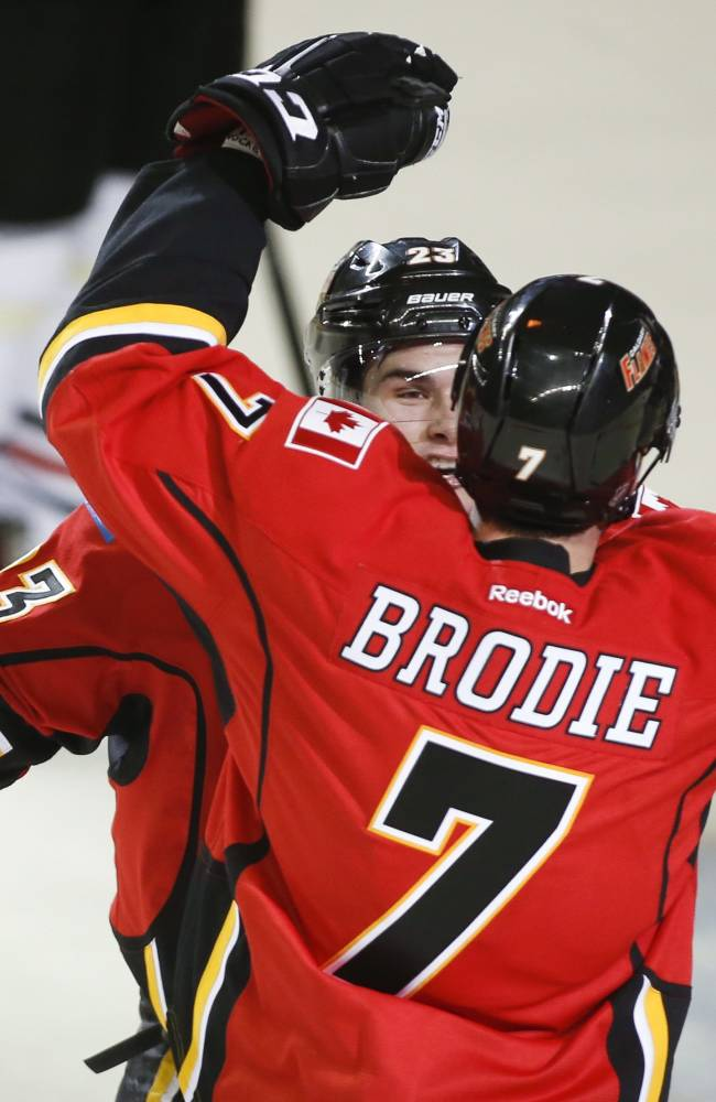 Calgary Flames' TJ Brodie, right, celebrates his game-wining goal with teammate Sean Monahan during overtime NHL hockey action in Calgary, Alberta, Tuesday, Jan. 28, 2014. The Calgary Flames beat the Chicago Blackhawks 5-4 in overtime