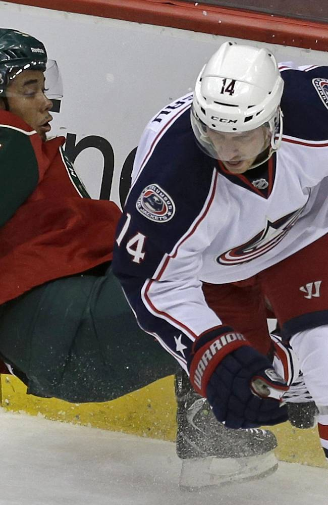 Minnesota Wild's Matthew Dumba, left is upended as he gets tangled up with Columbus Blue Jackets' Blake Comeau in pursuit of the puck behind the net in the first period of a NHL preseason hockey game, Tuesday, Sept. 17, 2013 in St. Paul. Minn
