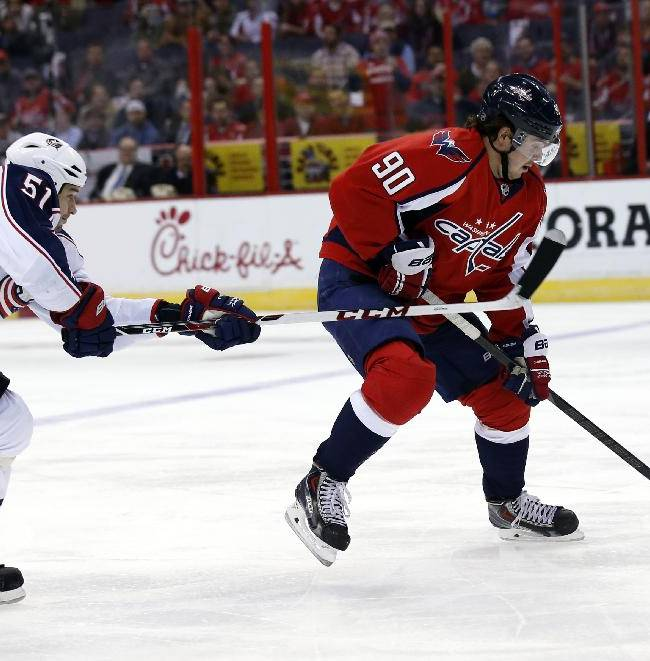 Columbus Blue Jackets defenseman Fedor Tyutin (51), of Russia, reaches for the puck controlled by Washington Capitals center Marcus Johansson (90), of Sweden, in the first period of an NHL hockey game Tuesday, Nov. 12, 2013, in Washington