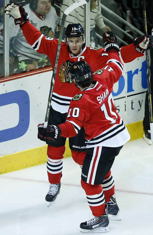 Chicago Blackhawks center Jonathan Toews, back, celebrates with teammate left wing Patrick Sharp (10) after Toews scored a goal during the third period of an NHL hockey game against the San Jose Sharks on Sunday, Nov. 17, 2013, in Chicago