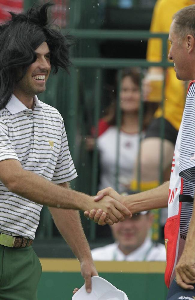 International team player Charl Schwartzel, left, of South Africa, wears a wig onto the first tee as he greets caddie Jim Mackay, who carries the bag for the United States' Phil Mickelson, before the start of the four-ball matches at the Presidents Cup golf tournament at Muirfield Village Golf Club Thursday, Oct. 3, 2013, in Dublin, Ohio