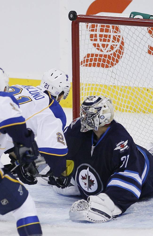 St. Louis Blues' Patrik Berglund (21) and Winnipeg Jets goaltender Ondrej Pavelec (31) watch as the rebound goes off the post during the first period of an NHL hockey game, Friday, Oct. 18, 2013 in Winnipeg, Manitoba