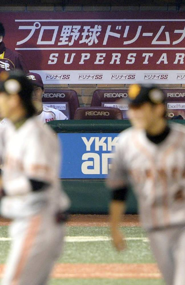 Rakuten Eagles starter Masahiro Tanaka, right, sits in the bench as Yomiuri Giants players, foreground, celebrate after their 4-2 victory in Game 6 of baseball's Japan Series at the Kleenex Stadium Miyagi in Sendai, northeastern Japan, Saturday, Nov. 2, 2013. The Giants handed Tanaka his first loss since Aug. 19, 2012