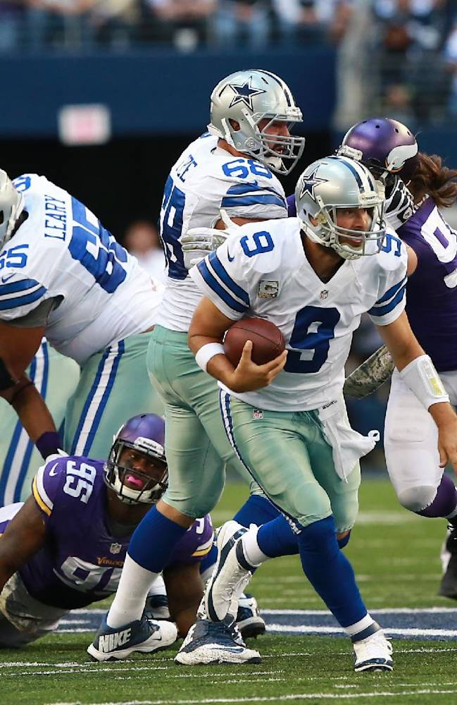 Dallas Cowboys quarterback Tony Romo (9) runs away from Minnesota Vikings defense for a first down during the second half of an NFL football game Sunday, Nov. 3, 2013, in Arlington, Texas