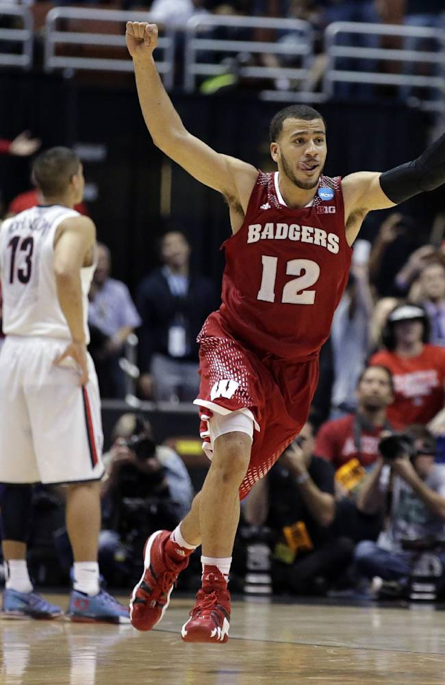 Wisconsin 's Traevon Jackson celebrates in front of Arizona's Nick Johnson (13) as time runs out in overtime of a regional final NCAA college basketball tournament game, Saturday, March 29, 2014, in Anaheim, Calif. Wisconsin won 64-63 in overtime