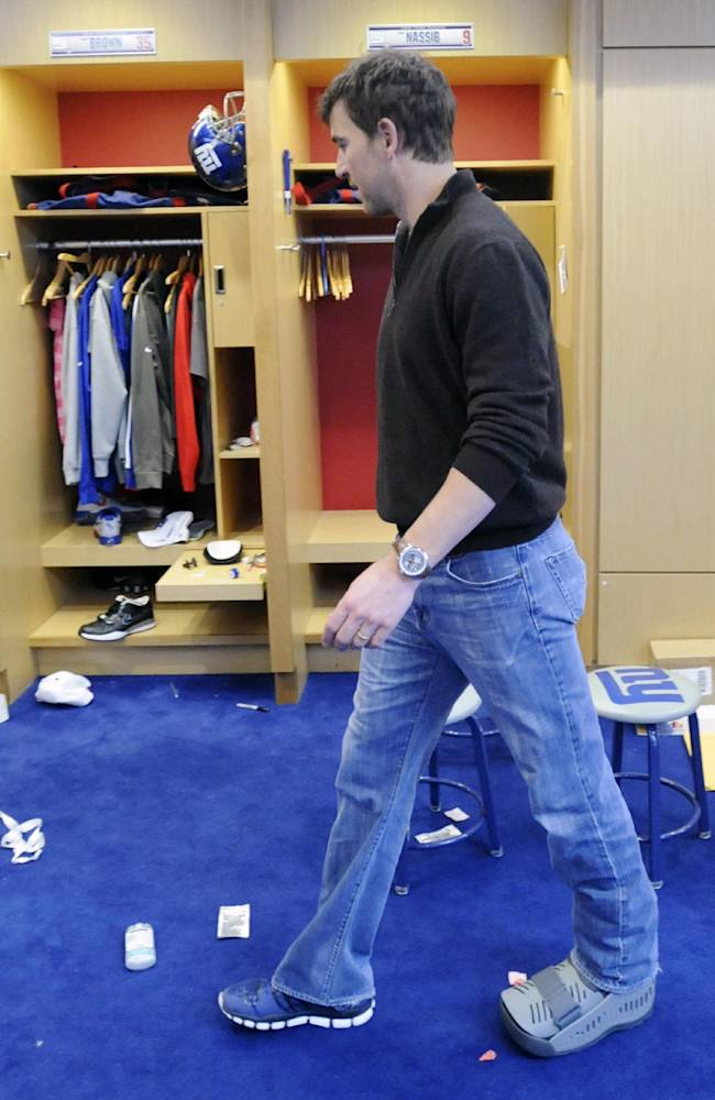 New York Giants quarterback Eli Manning leaves the lockeroom with a walking boot on his left foot after speaking to the media Monday, Dec. 30, 2013, in East Rutherford, N.J. Manning injured his ankle in the last game of the season against the Washington Redskins
