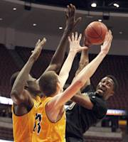 Cal Poly guard Dave Nwaba, right, passes the ball away from UC Irvine center Mamadou Ndiaye, left, and forward Mike Best during the first half of an NCAA college basketball game of the Big West Conference men's tournament in Anaheim, Calif., Friday, March 14, 2014. (AP Photo/Alex Gallardo)