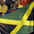A Jamaica soccer fan waves his national flag before the start of a 2014 World Cup qualifying soccer match between Jamaica and the United States in Kingston, Jamaica, Friday, June 7, 2013. (AP Photo/Andres Leighton)