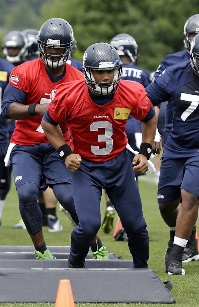 Seattle Seahawks quarterback Russell Wilson (3) leads players through a drill at an NFL organized team activity football practice Thursday, June 12, 2014, in Renton, Wash